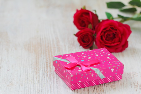 Fresh red roses and gift box on wooden table. St. Valentines Day concept. Stock fotó - 115731551