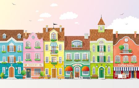 Staré historické domy, obchody a kavárny na ulici města s letní stromy a květiny