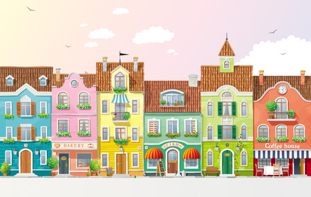 Old historical houses, shops and cafe at the city street with summer trees and flowers