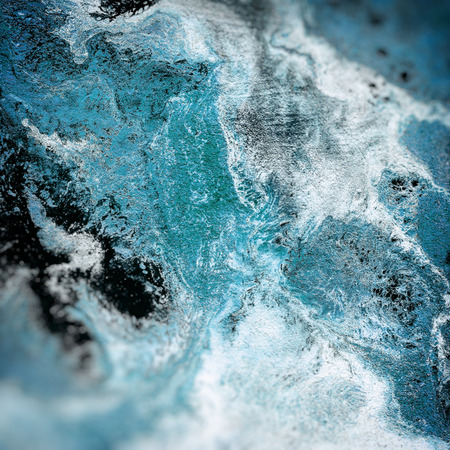 Abstract liquid blue background. Pattern with abstract frozen and black waves. Marble. Handmade surface. Liquid paint. Acrillic wallpaper. Mineral frost texture. Stock Photo