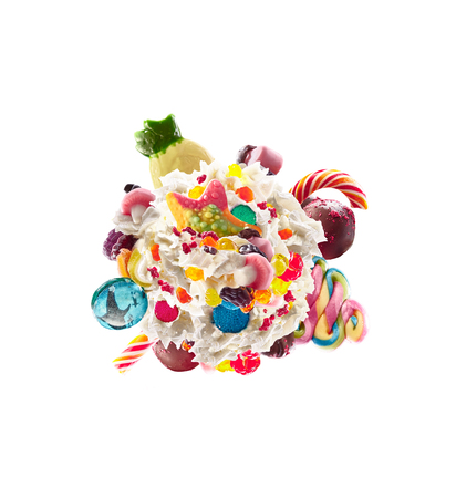 Milk shake with sweets and whipped cream, round form top view. Crazy freakshake food trend. Top view of whipped cream, full of berry and jelly sweets, chocolate candy. Colored whipped cream concept. Monster shake, freak shake concept isolated