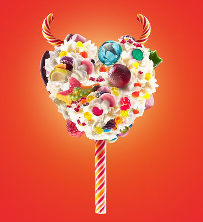 Devil heart Milk shake lollipop with sweets and whipped cream, front view. Sweet devil lollipop concept with whipped cream and devil horns, devil sweats. Front view of whipped cream of devils sweets, full of berry and jelly sweets. Whipped devil cream Stock Photo
