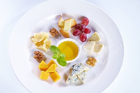 Different type of cheese with honey, grape, nuts on white plate. Top view. Blue cheese, cheddar, parmesan, maasdam and brie cheese slices Фото со стока