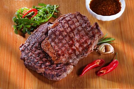 juicy delicious medium fried meat steak on a wooden cutting board, with pepper, garlic, herbs and tomato sauce. Steak for a restaurant on wooden background