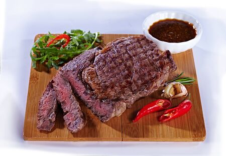 juicy delicious medium fried meat steak on a wooden cutting board, with pepper, garlic, herbs and tomato sauce. Steak for a restaurant on a white background