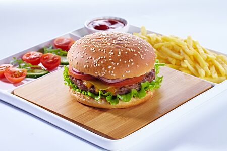 Juicy tasty hamburger on a wooden cutting board with french fried fries, vegetables and ketchup. Isolated composition on a white background and white serving tray.