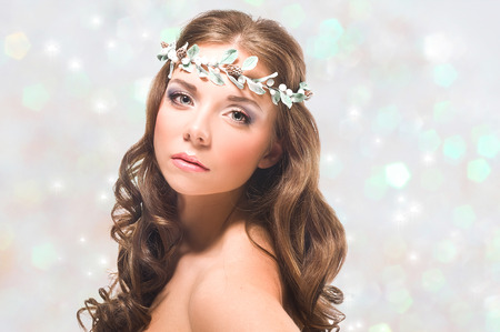 Portrait of a young girl with turquoise eyes on the silver shining background photo