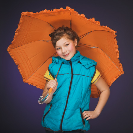 Little girl in a vest with an orange umbrella. photo