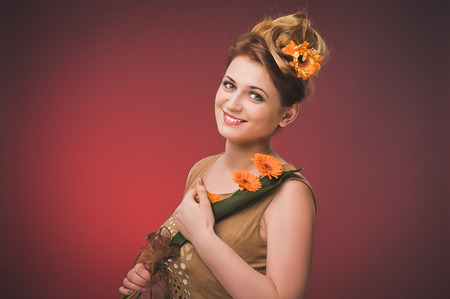 Attractive plus size model. Portrait of beautiful curly young blond woman with flowers in her hair posing on orange. photo