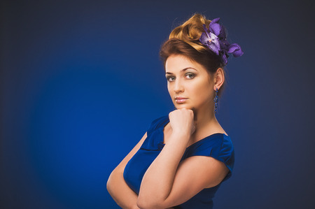 Attractive plus size model. Portrait of beautiful curly young blond woman with flowers in her hair posing on violet. photo