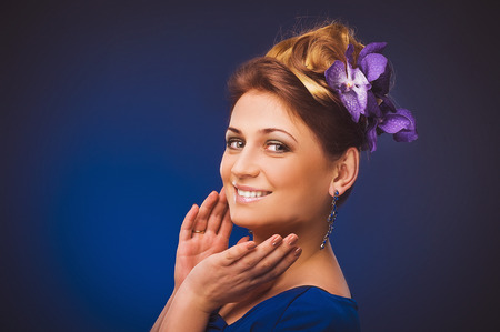 plus sized: Portrait of beautiful curly young blond woman with flowers in her hair posing on violet. Stock Photo