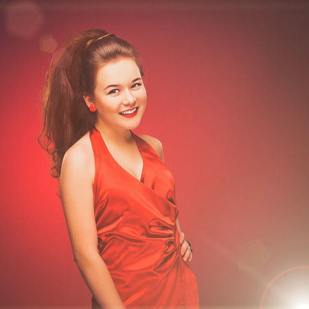 Stylized retro portrait of a young woman in red dress. photo