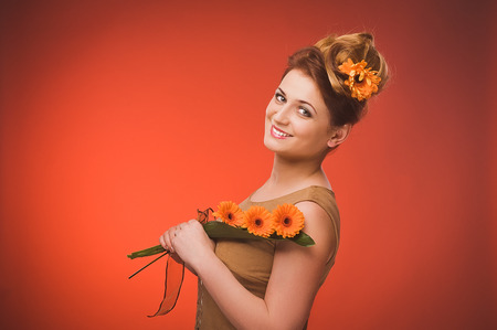 plus sized: Portrait of beautiful curly young blond woman with flowers in her hair posing on orange.
