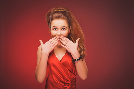 surprise face: Young girl in a red dress on a red background