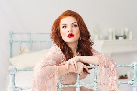 éxtasis: Mujer de pelo rojo romántica en vestido suave en habitación luminosa