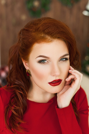 Woman in red dress and red lipstick on her lips smiling and looking in camera photo
