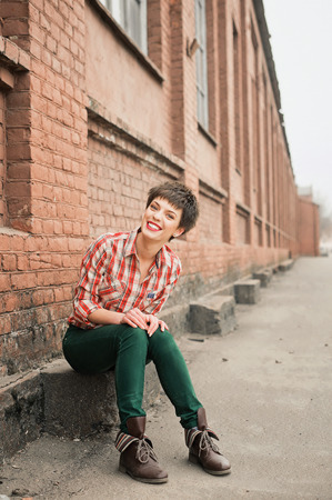 checkered scarf: Girl smiling friendly. Young woman plaid shirt jeans near brick wall. Looking into the camera. Stock Photo