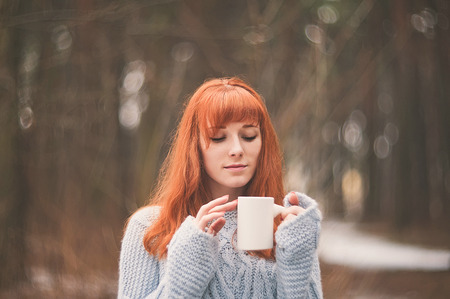 red tea: Hipster. Photo redheaded girl with a scarf. Forest.