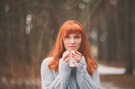 Hipster. Photo redheaded girl with a cup in his hand. Young woman drinking from a cup in the forest. photo