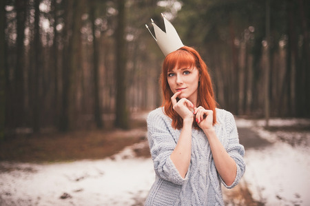 Hipster. Photo redheaded girl with a paper crown on his head. Young woman in forest. photo