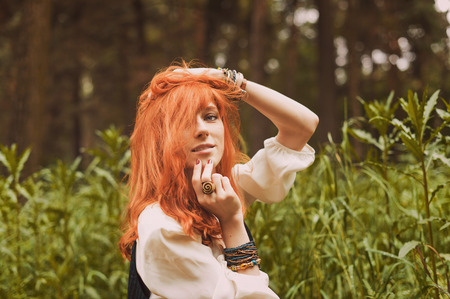 long skirt: Redhead hippie walks in summer forest. Young woman with long hair in a long skirt and blouse in Boho style. Photo of romantic girl in national dress. Stock Photo