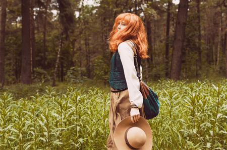 Red-haired girl walking in the woods in clothing style boho