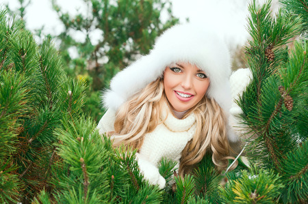 Beautiful girl in a white fur hat in the spruce forest photo