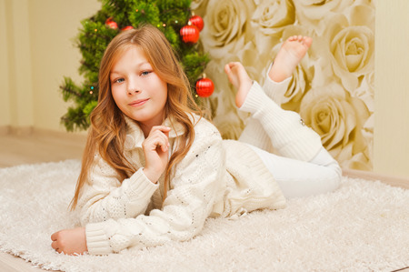 sweater girl: Girl lying on the carpet, looking at the camera and smiling. A child in a warm white sweater. Christmas tree. Teen in New Year clothes.
