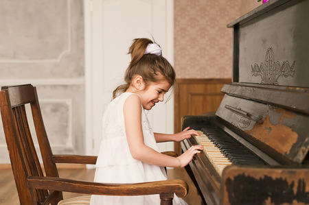 upright: Young girl playing piano Stock Photo