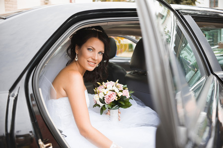 Young bride in a wedding car. Bridal bouquet.