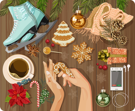 a table: Workplace concept. Top view with textured table, skating, gingerbread, fir branches, Christmas toys, balls, hands, Christmas decorations, snowflakes, coffee cup, candy, lollipop, flower, gift