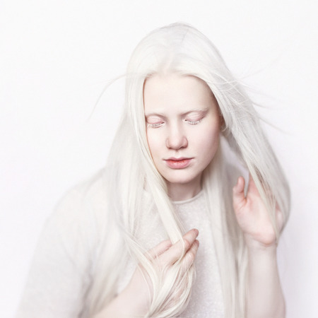 Albino girl with white skin, natural lips and white hair. Photo face on a light background. Portrait of the head. Blonde girl Stock Photo