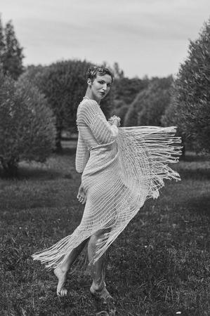 Fotografia in bianco e nero di una giovane donna che balla indossando un abito lungo lavorato a maglia. Immagine all'aperto