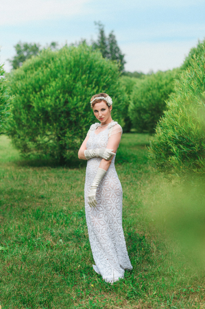Colorful photography of young posing woman wearing knitted long white dress.  Outdoors image