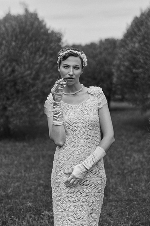 Black and white photography of young smoking woman wearing knitted long dress.  Outdoors image