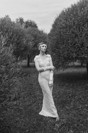 Black and white photography of young posing woman wearing knitted long dress.  Outdoors image 写真素材