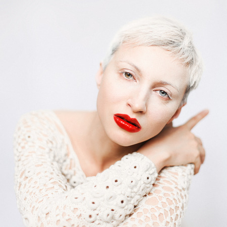 Woman with heterochromia of her eyes. Close Up portrait in light studio. Girl with white hairs and bright red lips.
