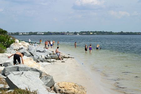 sun bathers: A scenic shot of a florida beach with people doing things like wading, rock climbing, fishing, sunbathing, and holding hands. Stock Photo