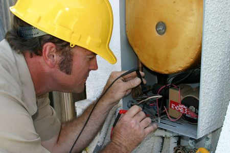 An air conditioning repairman, testing the voltage in a heat recovery unit.