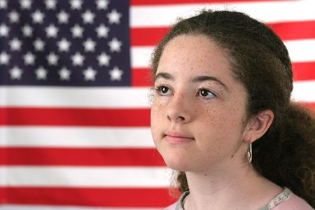 reverent: A teenaged girl posing in front of an American flag.