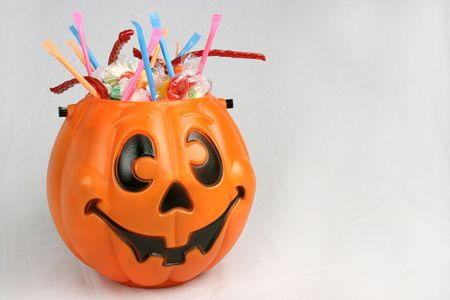 A Halloween pumpkin bucket brimming with candy against a white background.