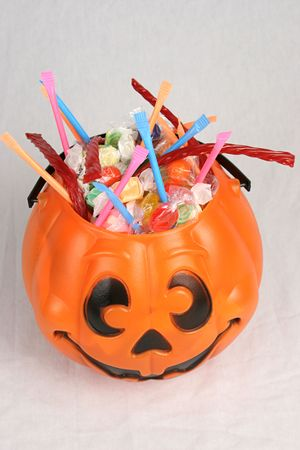 A Halloween pumpkin bucket brimming with candy against a white background. Top View.