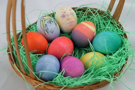 An Easter basket, filled with colored eggs and two eggs with characters drawn on them.