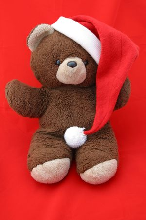A teddy bear wearing a santa hat against a red background. photo