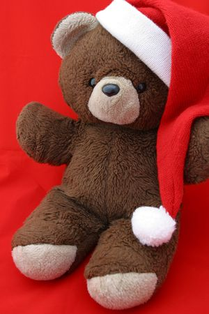 closeup, angled view of a teddy bear in a santa hat against a red background.