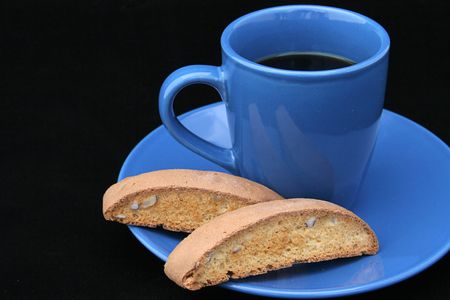 Black coffee in a bright blue cup, with biscotti on the side.  Photographed on black background. (room for text) photo