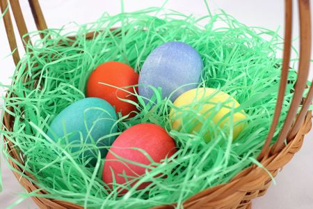 nestled: Five colorful eggs nestled in a basket of Easter grass.