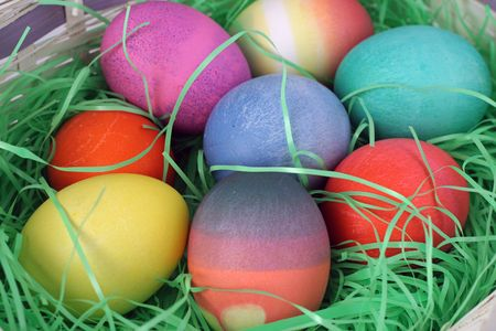 nestled:  closeup view of a group of colorfully dyed Easter eggs in a basket of grass.
