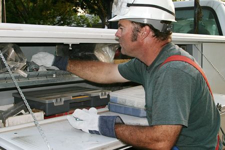 An electrician reaching for some tools on his service truck. Stock Photo