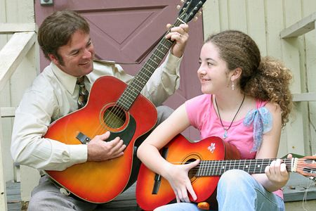 A father and daughter laughing together as they play guitars. photo